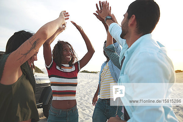 Exuberant young friends high-fiving on beach Exuberant young friends high-fiving on beach