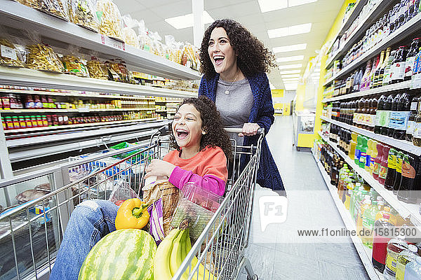 Playful mother pushing laughing daughter in shopping cart at supermarket