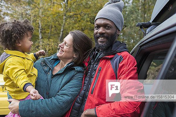 Portrait happy multiethnic family outside car