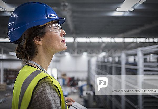 Smiling  confident female supervisor in hard-hat looking up in factory
