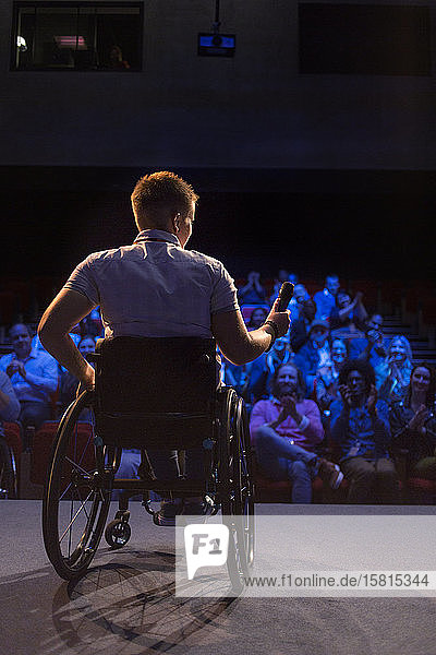 Female speaker with microphone in wheelchair on stage