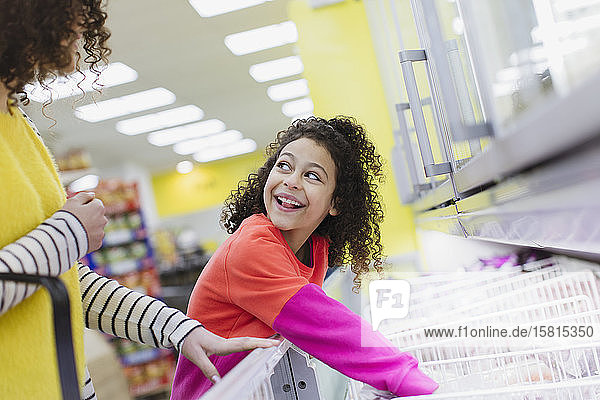 Mother and daughter shopping frozen foods in supermarket