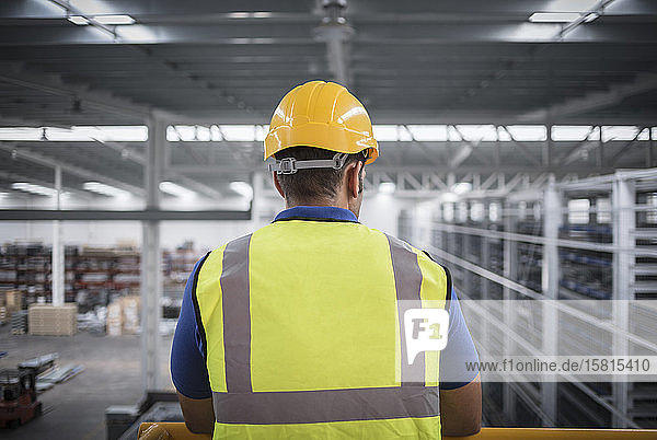 Male supervisor watching factory from platform Male supervisor watching factory from platform