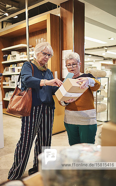 Senior women with smart phone shopping in home good store