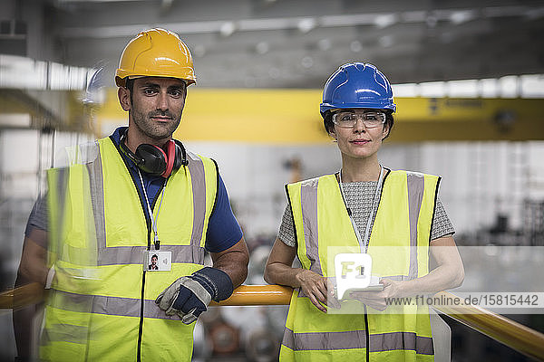 Portrait confident supervisors with digital tablet on platform in factory