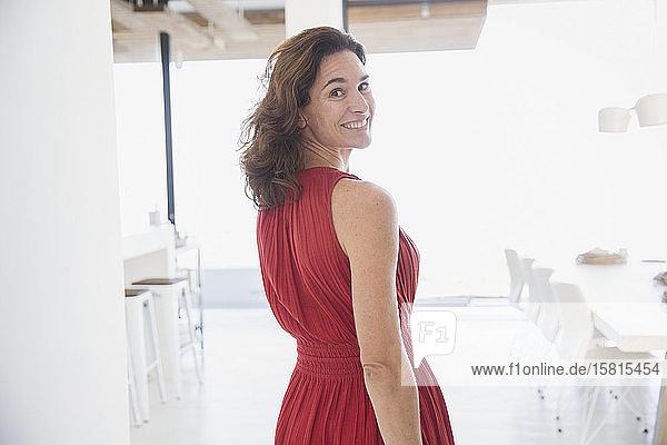 Portrait smiling  confident brunette woman in red dress walking  looking over shoulder at home Portrait smiling, confident brunette woman in red dress walking, looking over shoulder at home