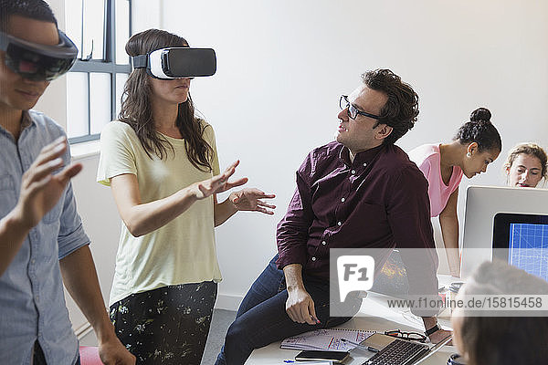 Computer programmers testing virtual reality simulator glasses in office Computer programmers testing virtual reality simulator glasses in office