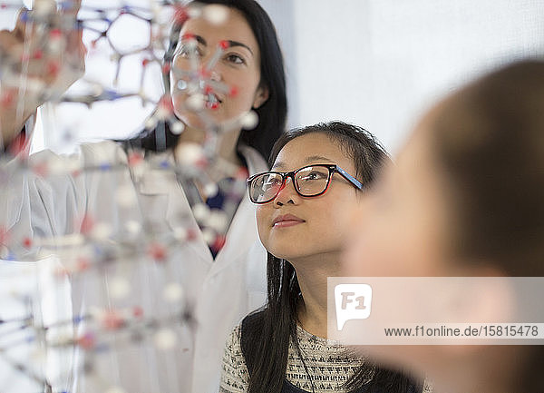 Female teacher and curious girl students examining molecular structure in laboratory classroom
