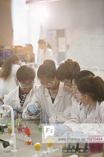 Students conducting scientific experiment  pouring liquid in beaker in laboratory classroom Students conducting scientific experiment, pouring liquid in beaker in laboratory classroom