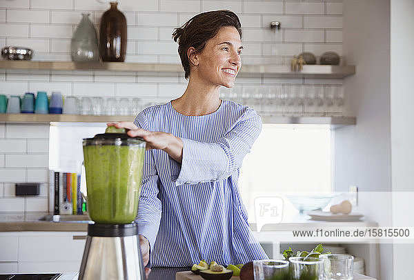 Smiling brunette woman making healthy green smoothie in blender in kitchen Smiling brunette woman making healthy green smoothie in blender in kitchen
