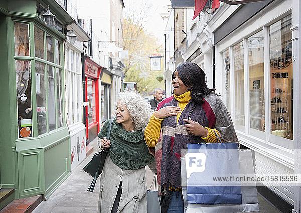 Senior women friends window shopping outside storefront