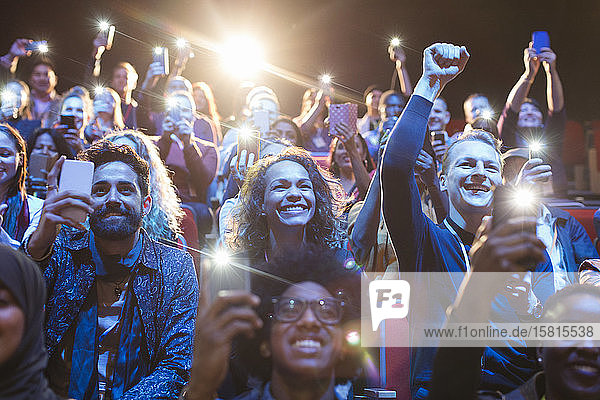 Excited audience with smart phone flashlights cheering Excited audience with smart phone flashlights cheering