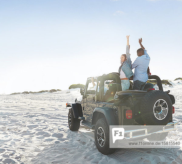 Enthusiastic young friends with arms raised  enjoying road trip on sunny beach Enthusiastic young friends with arms raised, enjoying road trip on sunny beach