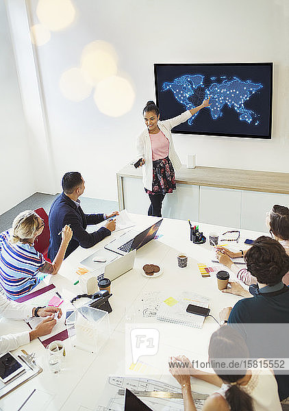 Businesswoman at television screen leading conference room meeting