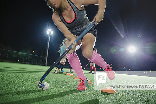 Young female field hockey players practicing sports drill on field at night