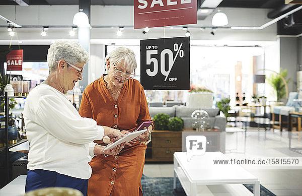 Senior women with digital tablet shopping in home decor shop Senior women with digital tablet shopping in home decor shop
