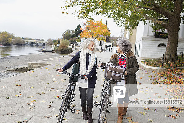 Smiling active senior women walking bicycles in autumn park