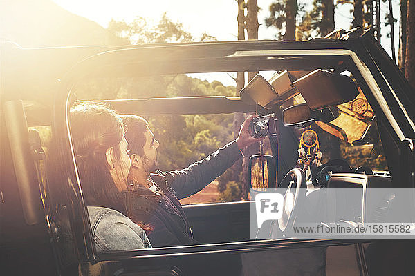 Junges Paar mit digitaler Tablet-Kamera nimmt Selfie im Jeep in sonnigen Wäldern