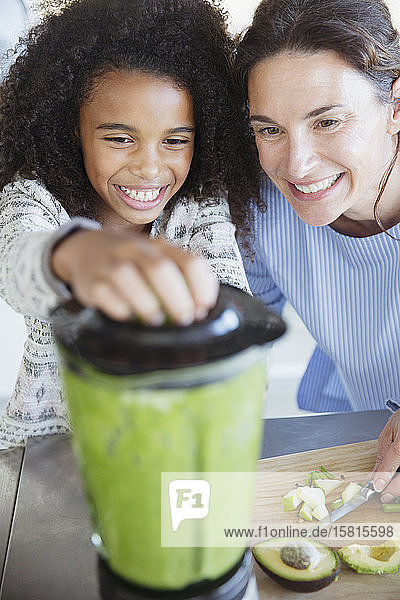 Mother and daughter making healthy green smoothie in blender Mother and daughter making healthy green smoothie in blender