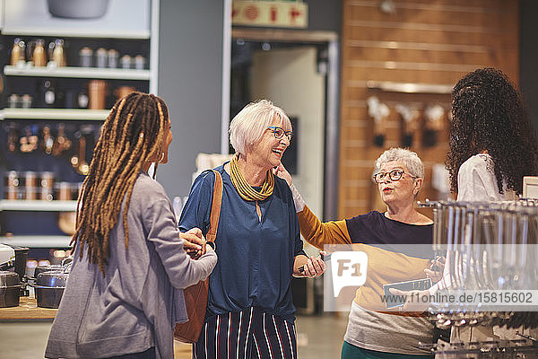 Happy women talking shopping in home goods store