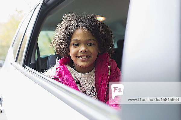 Portrait happy girl riding in back seat of car Portrait happy girl riding in back seat of car