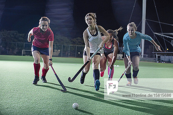 Young female field hockey players running for the ball  playing on field at night Young female field hockey players running for the ball, playing on field at night