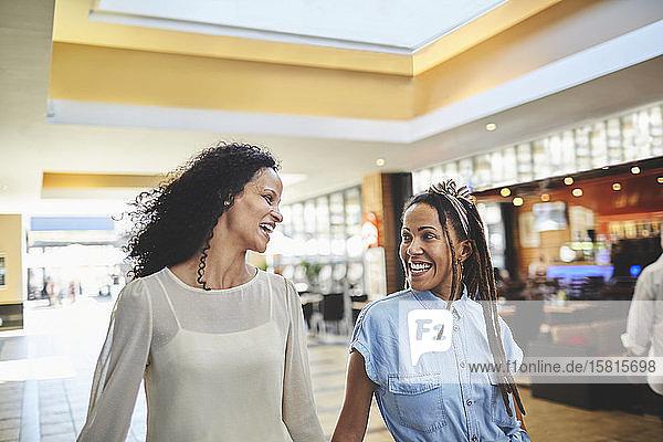 Happy women friends shopping in mall