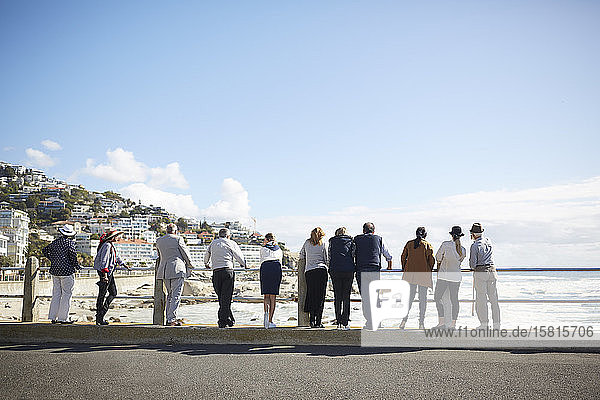Active senior tourist friends looking at sunny ocean view