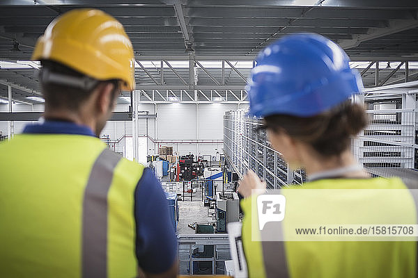 Supervisors talking and pointing on platform in factory
