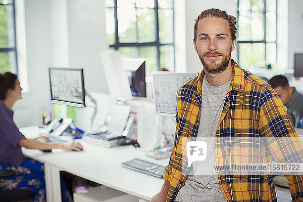 Portrait confident designer in open plan office