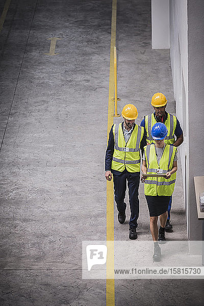 Supervisor and workers with digital tablet walking in factory Supervisor and workers with digital tablet walking in factory