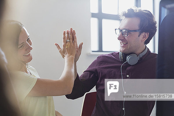 Enthusiastic creative business people high-fiving in office