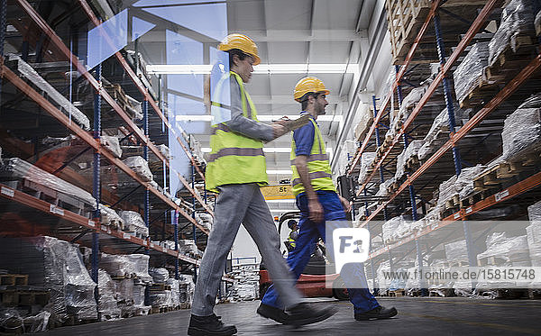 Workers with clipboard walking in warehouse Workers with clipboard walking in warehouse