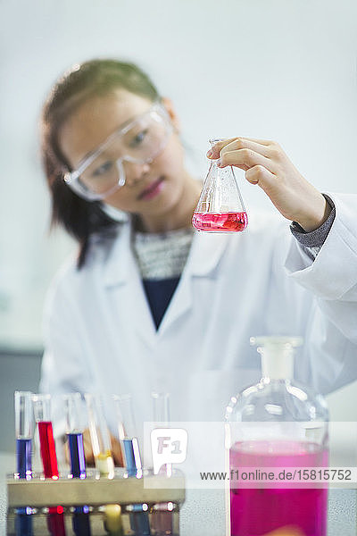 Girl student examining pink liquid  conducting scientific experiment in laboratory classroom