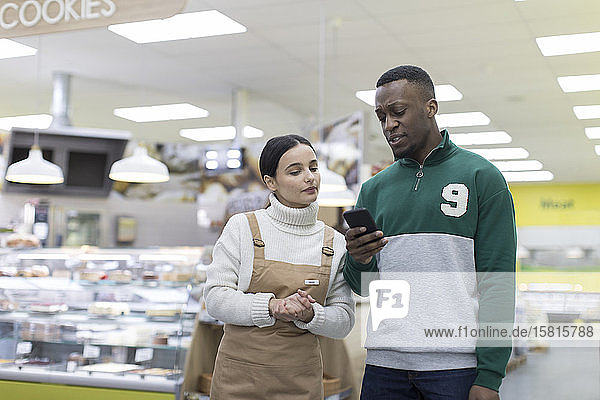 Female grocer helping male customer with smart phone in supermarket