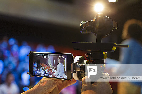 Cameraman with smart phone and equipment videoing speaker on stage Cameraman with smart phone and equipment videoing speaker on stage
