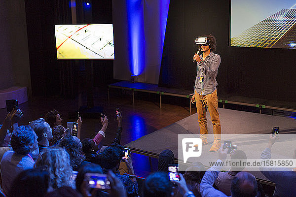 Audience watching male speaker with virtual reality simulator glasses on stage