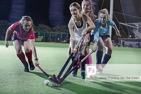 Female field hockey players playing on field