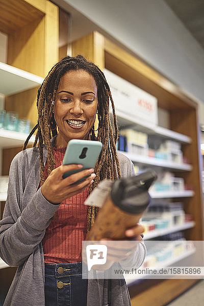 Smiling woman with smart phone shopping in home goods store