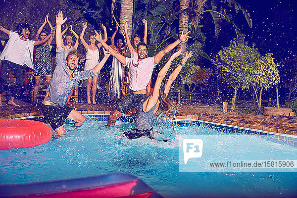 Portrait exuberant young friends jumping into swimming pool at night