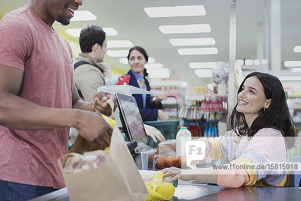 Friendly cashier helping customers at supermarket checkout