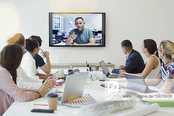 Designers video conferencing with colleague in conference room meeting