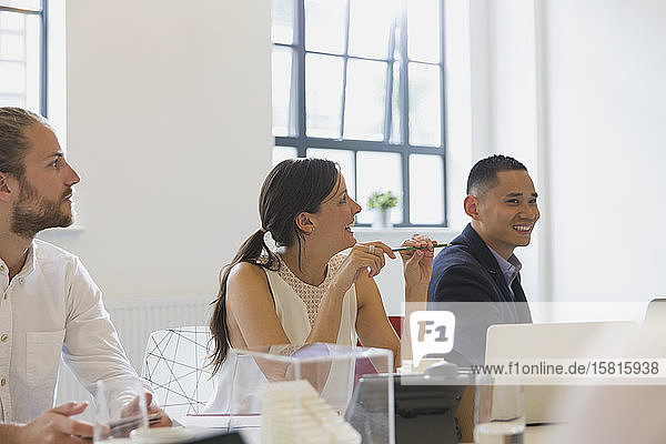 Female architect listening in conference room meeting Female architect listening in conference room meeting