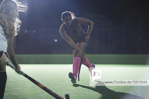 Determined young female field hockey player running with hockey stick  playing on field at night