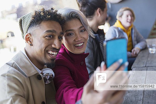 Smiling young couple taking selfie in camera phone