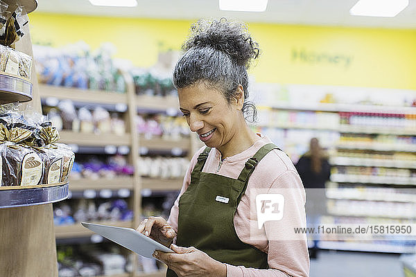 Smiling female grocer with digital tablet working in supermarket Smiling female grocer with digital tablet working in supermarket