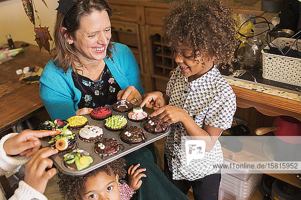 Happy mother and children with decorated Halloween cupcakes