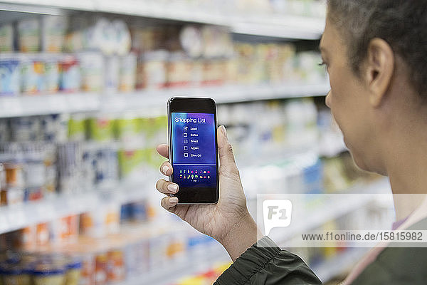 Woman with digital shopping list on smart phone in supermarket