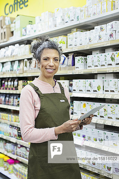 Portrait smiling  confident female grocer with digital tablet working in supermarket