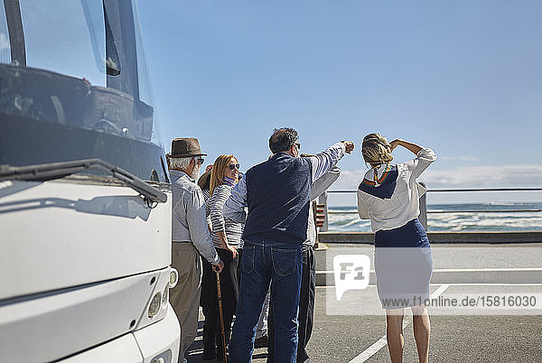 Tour guide and active senior tourists looking at ocean outside tour bus